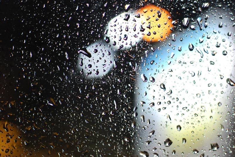 Rain drops on window with road light bokeh background stock photo