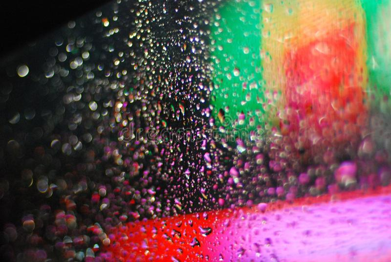 Rain drops on window with road light bokeh background stock photography