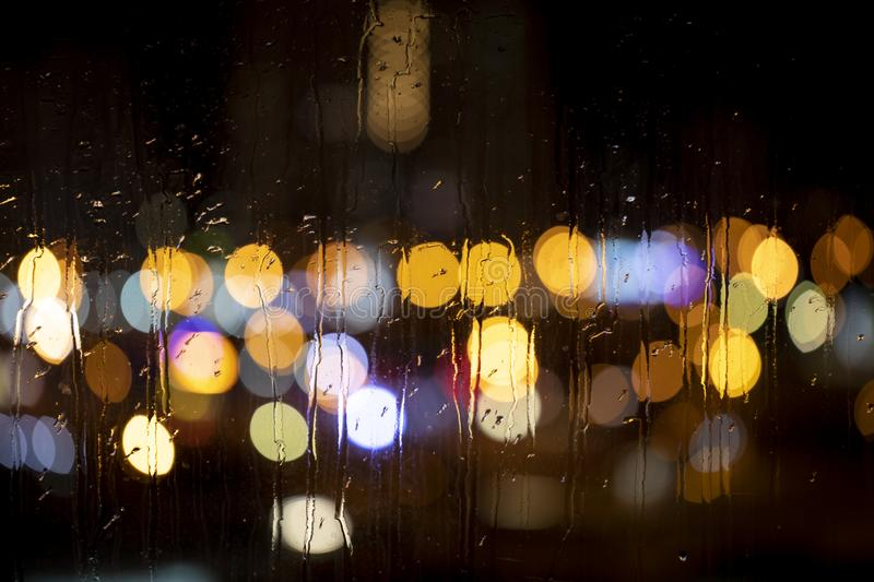 Rain drops on window with road light bokeh stock image