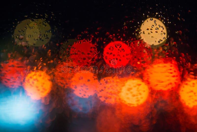 Rain drops on window with street bokeh lights. Rain drops on window with street bokeh lights, colorful street lights royalty free stock photo
