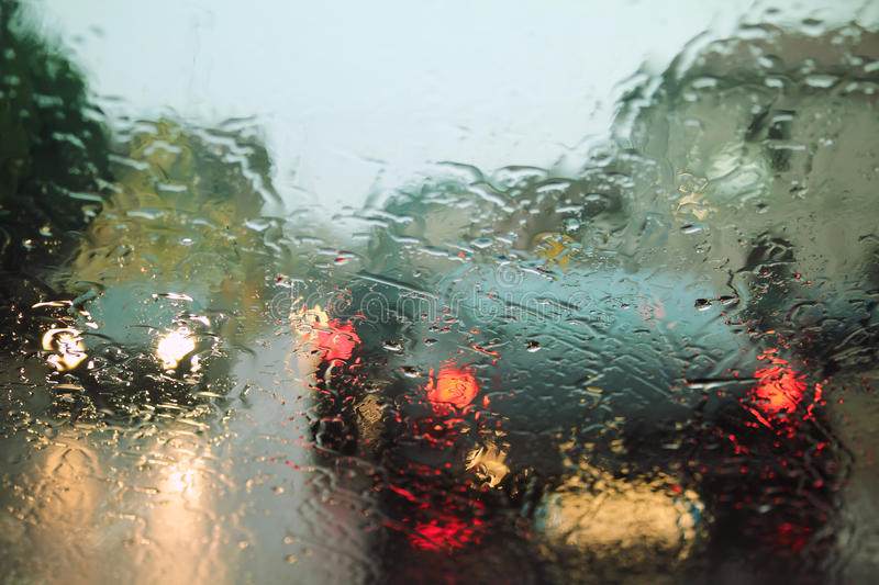 Rain drops on windshield. Driving with rain drops on windshield in the city royalty free stock images