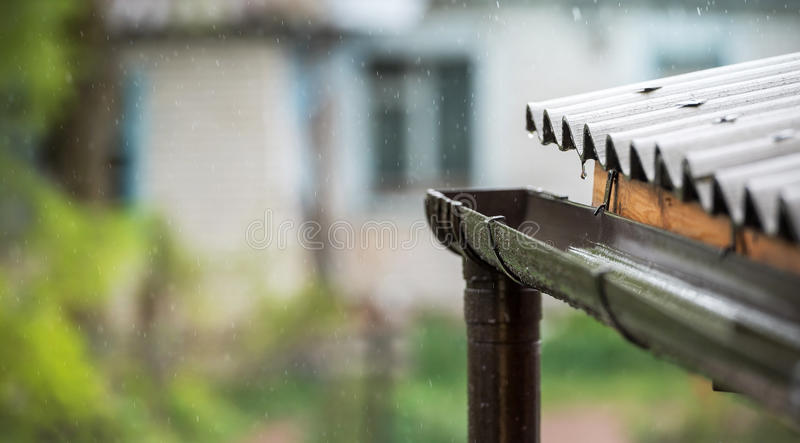 Rain falls from the roof into the drainpipe.  royalty free stock photography