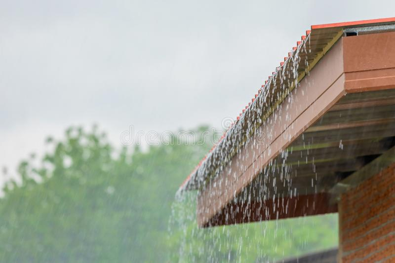 Rain flowing down from the roof house. In rainy season royalty free stock image