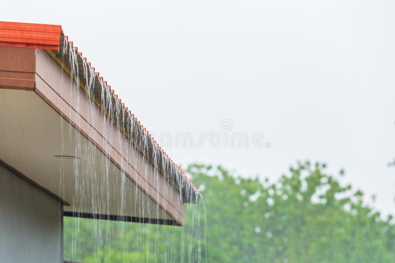 Rain flowing down from the roof house. In rainy season royalty free stock photos