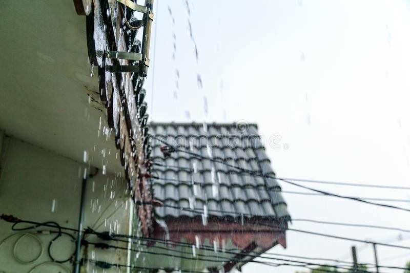 Rain water falling from old roof when rain falling. Rain flows down from a old roof during heavy rainfall royalty free stock photos