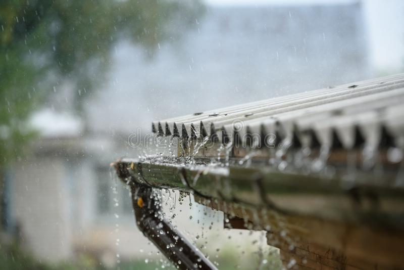 Rain flows down from a roof down.  stock image