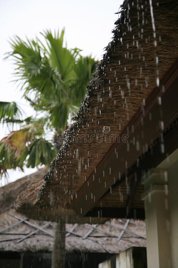 Rain flows down from a roof down stock image