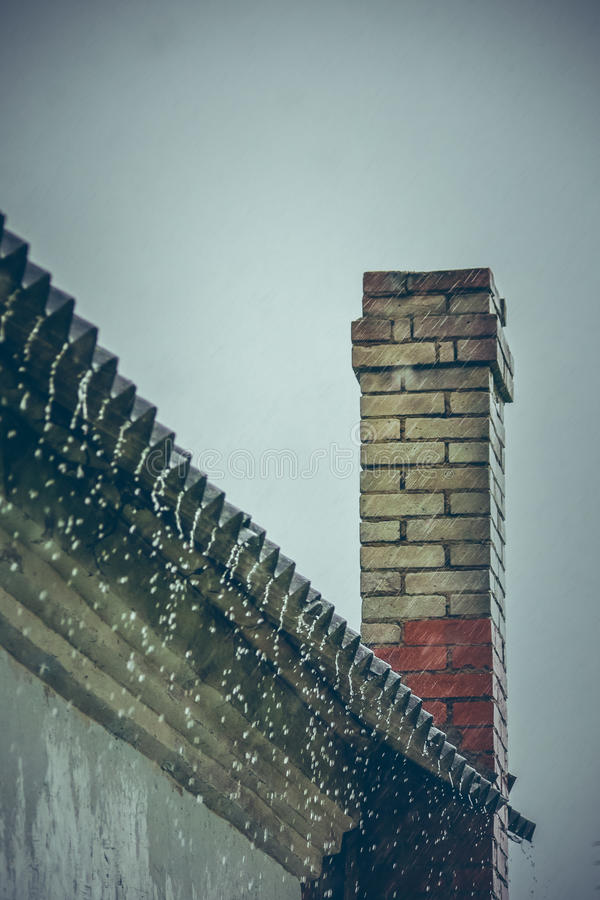 Rain flows down from a roof down stock photos