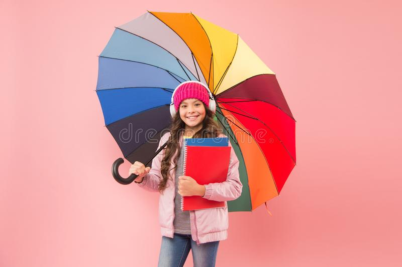 Rain forecast on September 1. Cute schoolgirl colorful umbrella on September 1. Small child go to library on September 1 royalty free stock photo