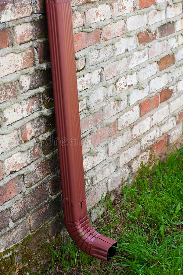 Rain gutter on brick house. A new, rust colored rain gutter is installed on a brick wall or house stock image