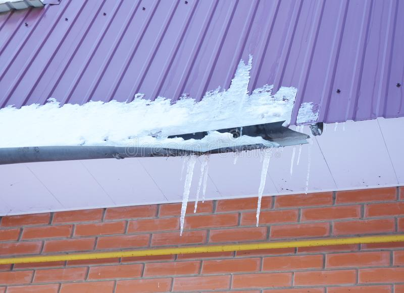 Rain Gutter damaged by ice and snow. Broken roof gutter pipeline by icicles stock image