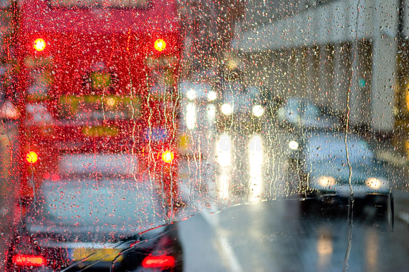 Rain in London view to red bus through rain-specked window royalty free stock photos
