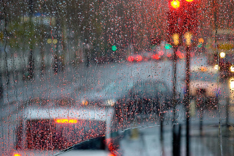 Rain in London view to red bus through rain-specked window royalty free stock image