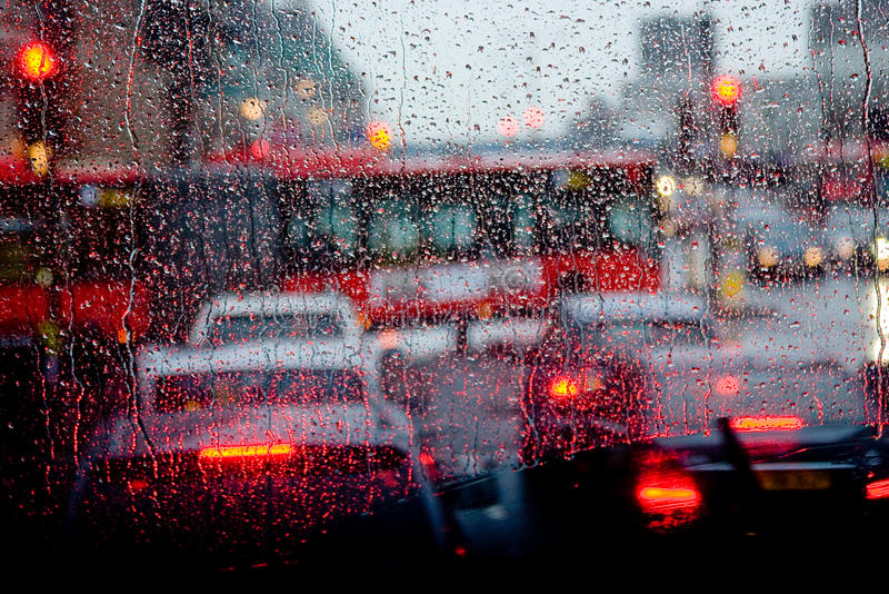 Rain in London view to red bus through rain-specked window stock photography