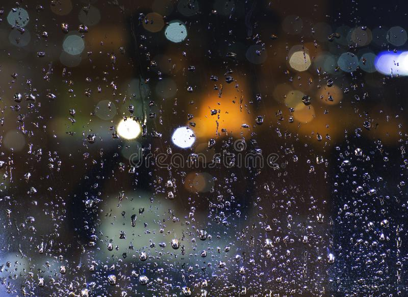 Rain outside. Drops on a window pane at night. Bad weather in the city. Lantern light defocused in beautiful bokeh. Rain outside. Drops of water on a window pane stock image