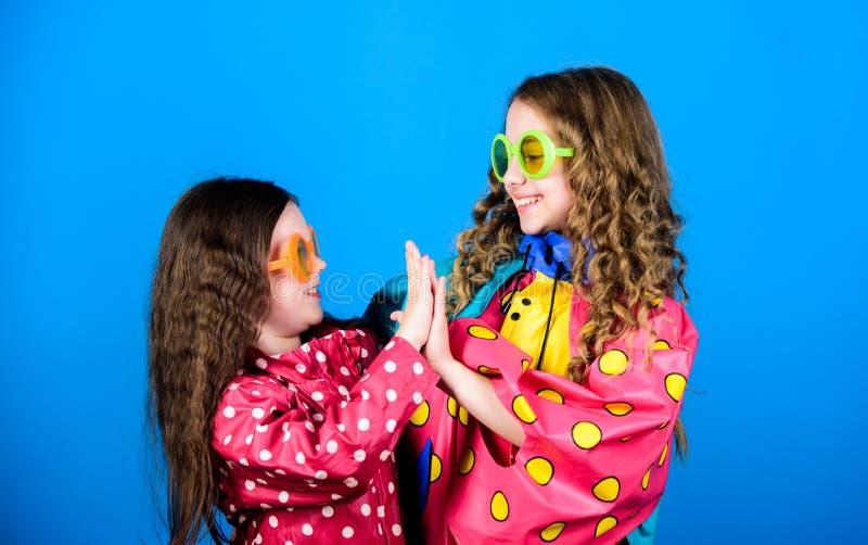 Rain protection. Rainbow. autumn fashion. cheerful hipster children, sisterhood. having fun. family bonds. Small girls. In raincoat and glasses. happy small stock photo