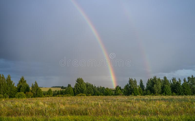 Rain and rainbow over fields and tree planting.  stock image