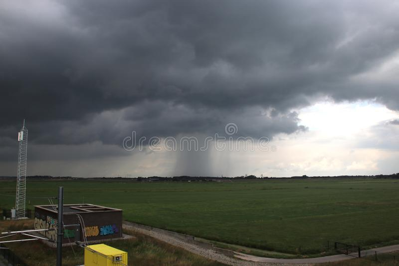 Rain shower over the city of Kampen with dark cumulus clouds in the Netherlands, stock photo