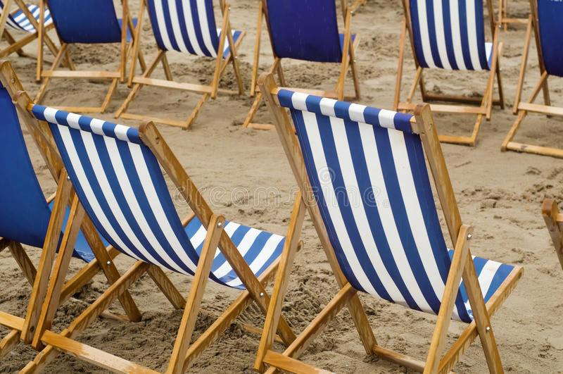 Rain soaked deck chairs stock image