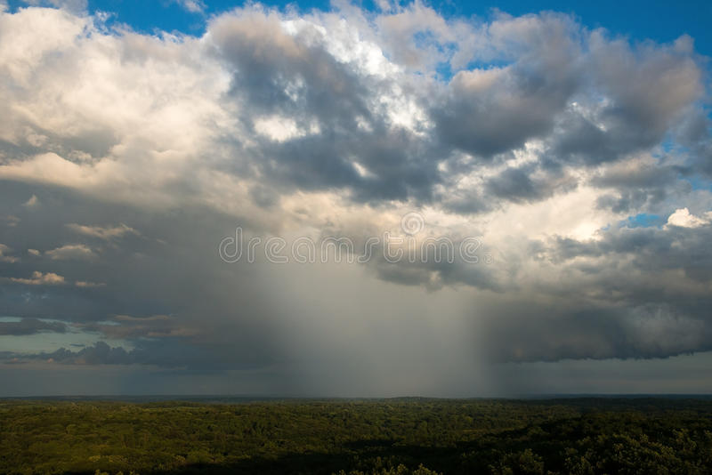 Rain Storm Cloud, Clouds, Weather. Passing rainstorm weather. Rain and clouds fall to earth as a cloudburst rains down on the land royalty free stock photos