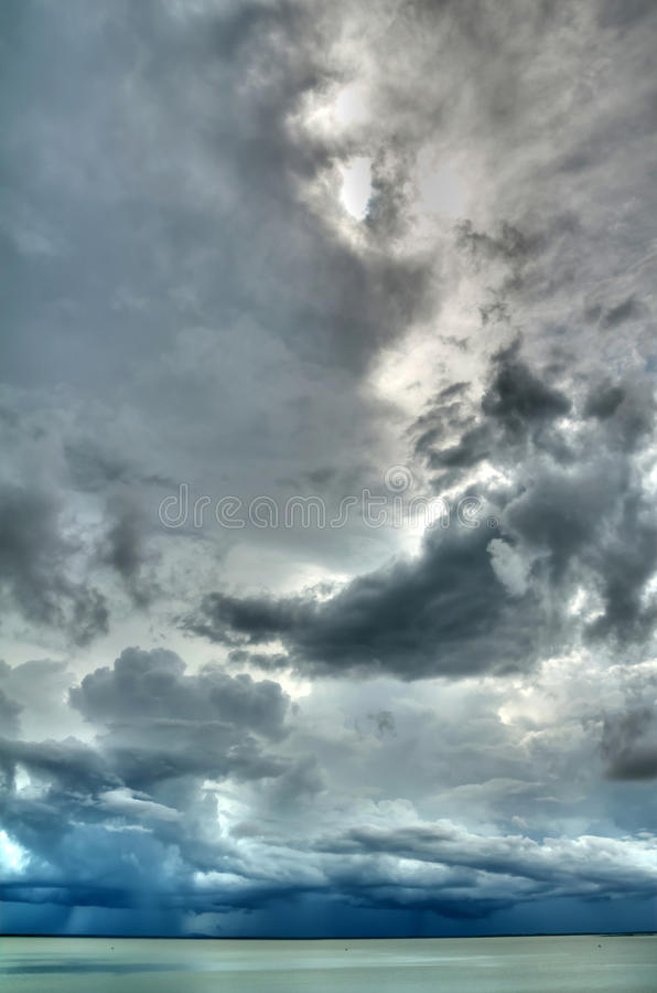 Rain storm cloud over the lake (HDR). A photo of rain cloud over the lake was shot during the rain storm forming stock photos