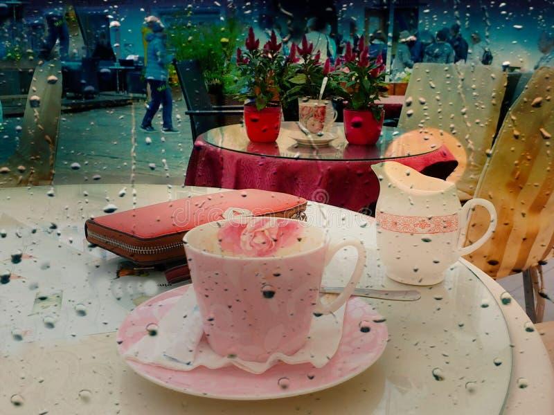Rain Street Cafe na mesa, xícara de café e flores rosa, tablete de coral rosa sobre a mesa e tecido de cadeira amarela, café da imagem de stock royalty free
