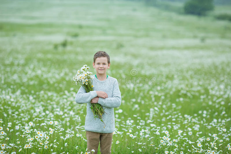 Rain and sunshine with a smiling boy holding an umbrella and running through a meadow of wildflowers dundelions chamomile daisy an. D holding bouquet stylish royalty free stock photos