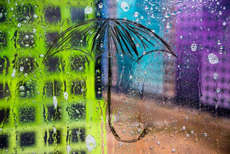 Rain, the umbrella is painted on glass stock photos