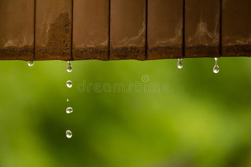 Rain water droplets coming down from rusted metal roof royalty free stock images