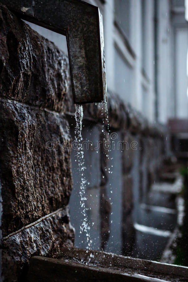 Rain water flowing from metal downspout during a flood. concept of protection against heavy downpours stock photos