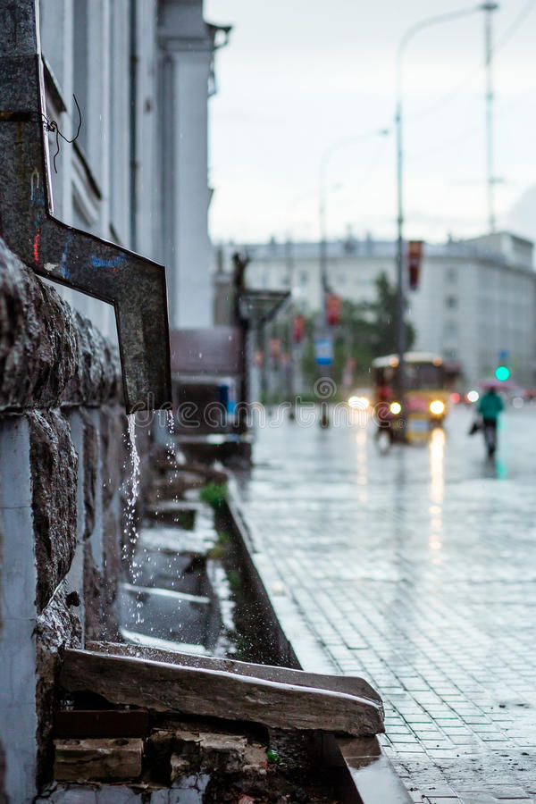 Rain water flowing from metal downspout during a flood. concept of protection against heavy downpours stock images