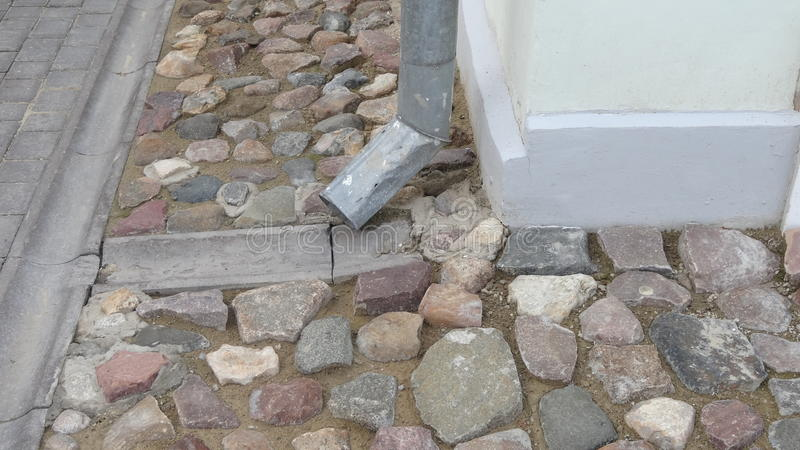 Rain water flowing from metal downspout during a flood. concept of protection against heavy downpours. stock image
