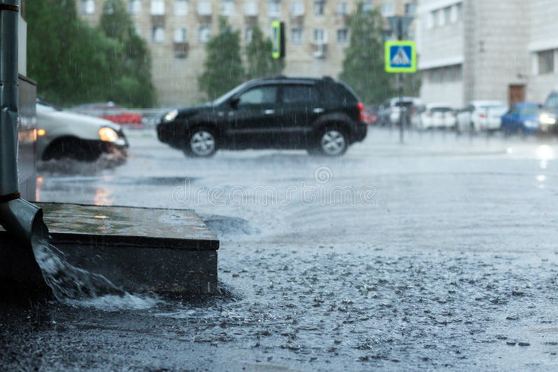 Rain water flowing from metal downspout during a flood. concept of protection against heavy rains. stock photos