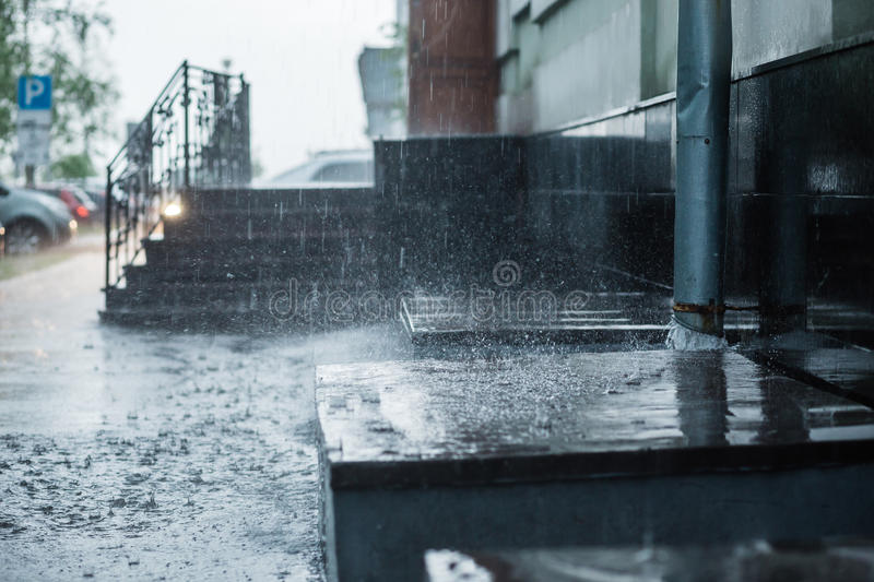 Rain water flowing from a metal downspout during a heavy rain. concept of protection against heavy rains royalty free stock images