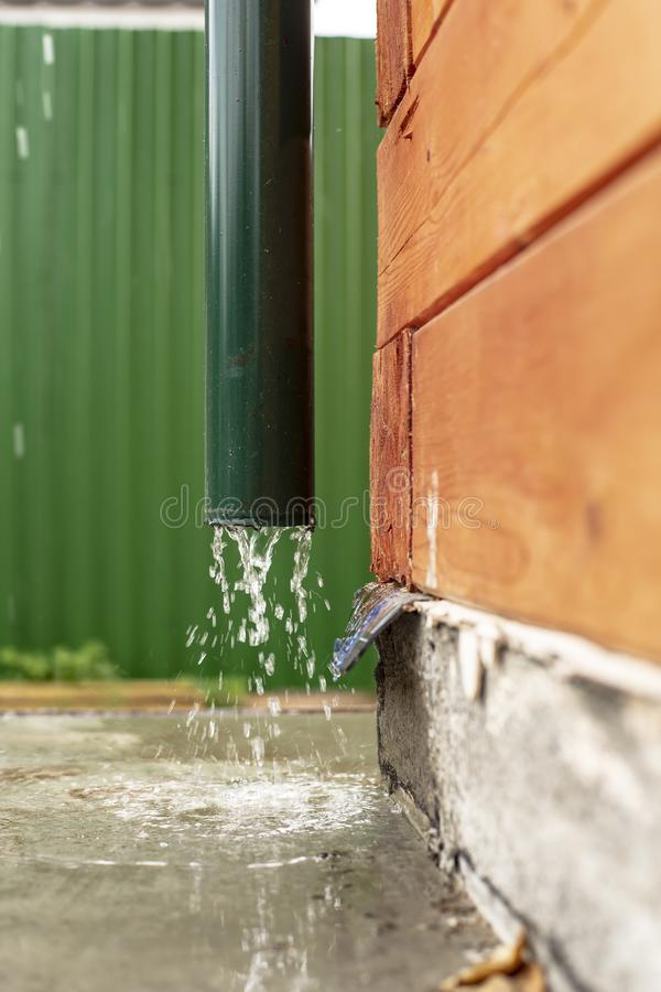 Rain water flows from a drainpipe to a concrete foundation, a wooden house, against a green fence royalty free stock photo