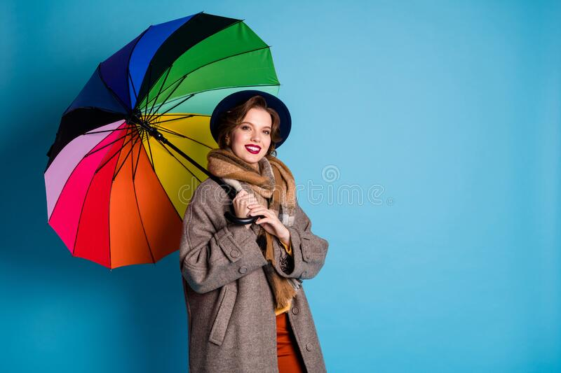 Rain will not stop me. Photo of pretty traveler lady hold colorful parasol walking down street wear stylish casual long stock photography