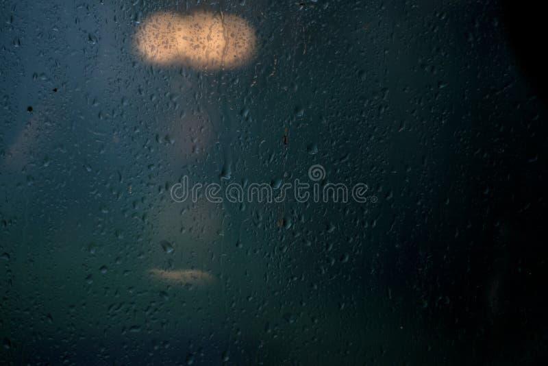 Rain on window. Rain on a window with lights glowing inside royalty free stock image
