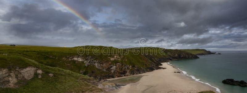Rainboe sobre la playa escocesa imagen de archivo