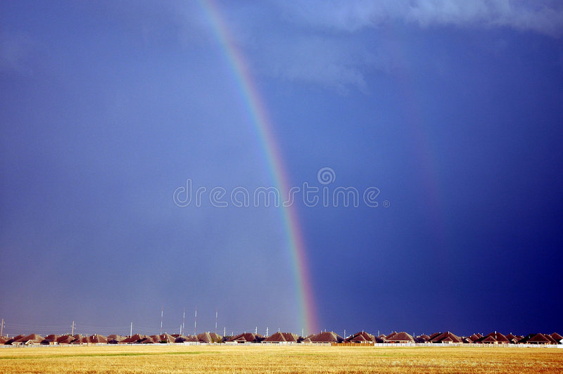Rainbow. Over houses in a storm filled sky stock photos