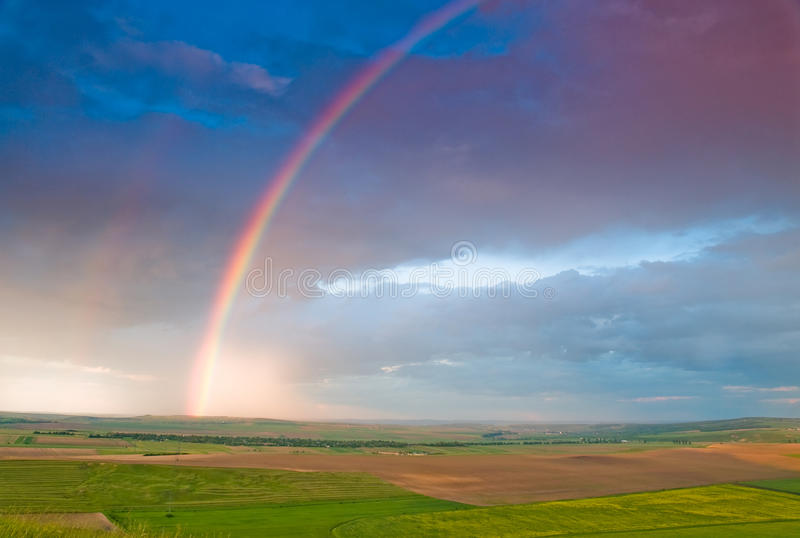 Rainbow with rain clouds and blue sky royalty free stock photography