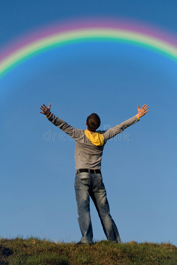 Rainbow. The man admires with a rainbow