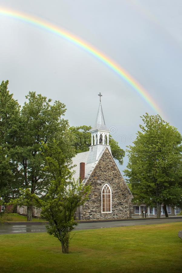 A rainbow above the Anglican stone-field church, St. Peter`s of Cookshire-Eaton in Estrie, Quebec, Canada stock photos
