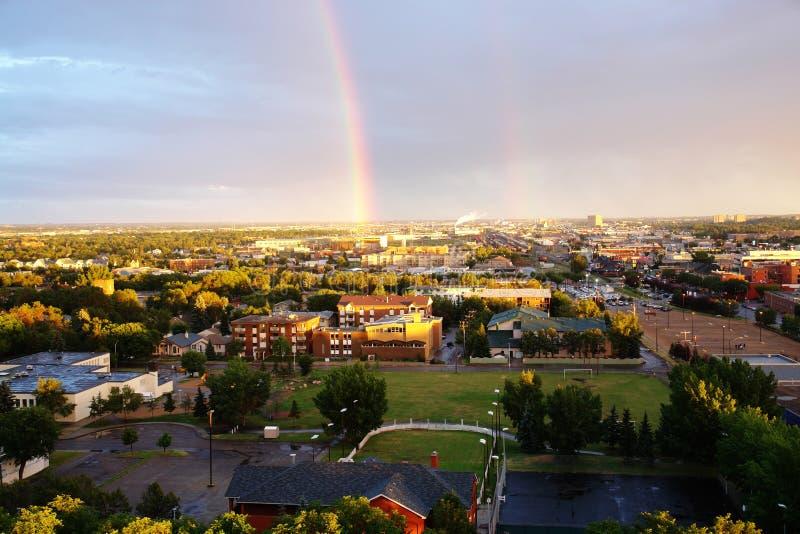 Rainbow above city edmonton stock photos