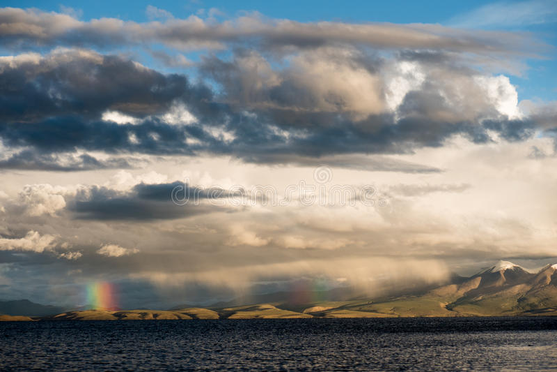Rainbow above Mountain Lake Manasarovar Himalayas Tibet. Mountain lake Manasarovar lies at 4,590 metres above mean sea level. Manasarovar is said to be the stock photography