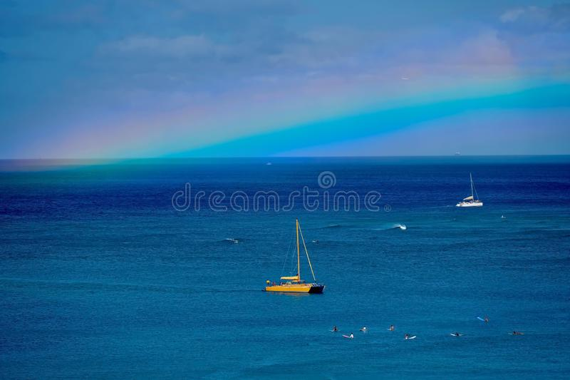 Rainbow above the ocean with catamaran, boat and surfers on waves. stock images