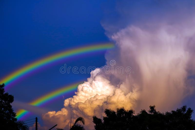 rainbow appears in sky after the rain and back on sunset cloud stock photos