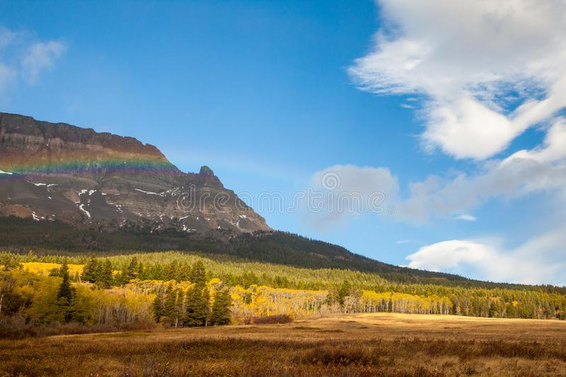Rainbow on an autumn day in front of a mountain near Saint Mary royalty free stock images