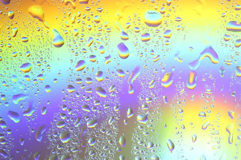 Rainbow background - water drops on the glass and color illumination royalty free stock photography