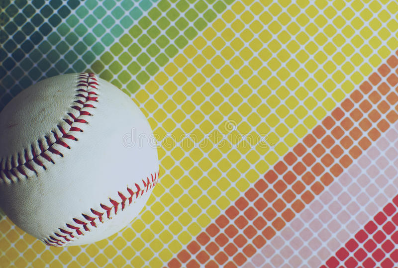 Rainbow background with white baseball. Rainbow colored geometric background with white baseball laying on top. Happy feelings for sports and athletic background royalty free stock images