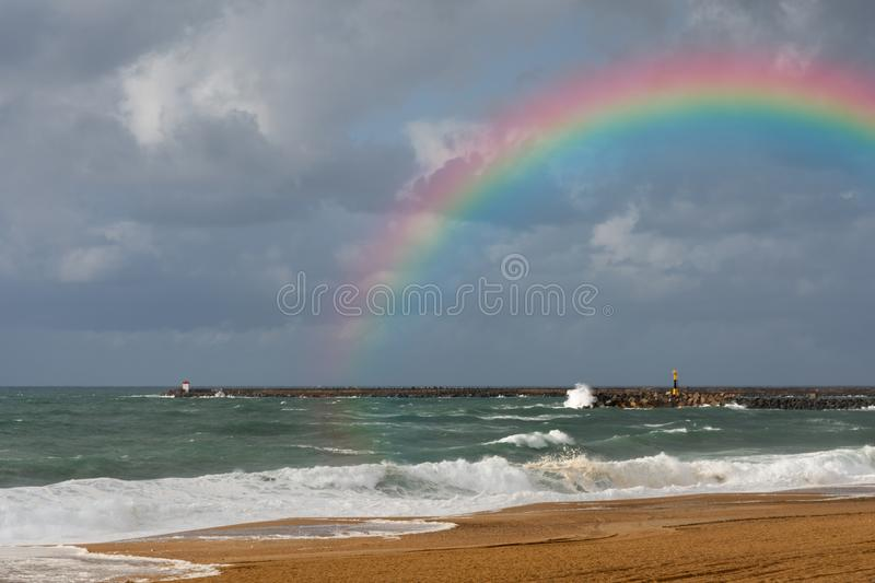 Rainbow on the beach of Anglet after the storm. After a storm, a rainbow formed on the beach of Anglet in the French Basque country